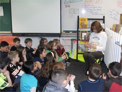 Ms. Tindera reads to Mrs. LaGruth's class